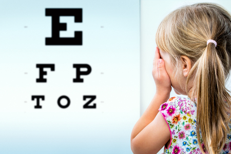 facing backwards: Close up rear view of girl testing eyesight. Infant closing one eye with hand looking at vision test chart. Stock Photo