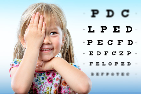 Cute little girl reviewing eyesight.Girl closing one eye with hand reading block letters on vision chart with focus point.