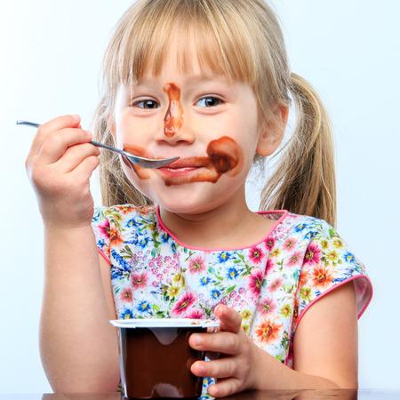 아침에 귀여운 소녀 먹는 초콜릿 요구르트의 초상화를 닫습니다. 초콜릿과 장난 꾸러기 표정으로 지저분한 얼굴.