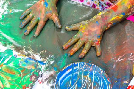 body paint: Cierre de vista superior de la pintura manos del niño en la mesa. Pintura abstracta con las manos cubiertas de pintura.