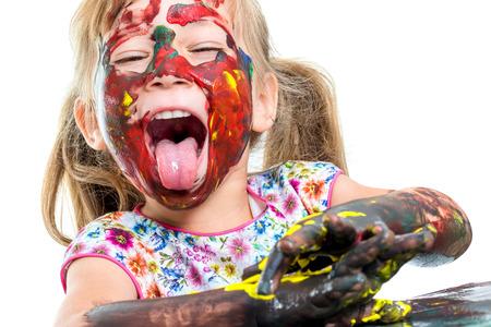 색 페인트로 엉망이 어린 소녀의 초상화를 닫습니다. 소녀 흰색 배경에 tongue.Isolated 튀어 나와 재미 있은 얼굴을하고.