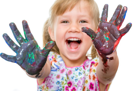 infant school: Close up portrait of shouting little girl showing hands messed with color paint.Isolated on white background.