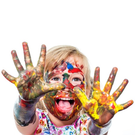 finger in mouth: Close up portrait of shouting Little Girl messed with color paint.Infant showing hands covered with paint. Isolated on white background. Stock Photo