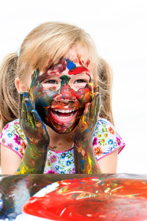 messed: Close up portrait of little girl with painted face. Laughing infant with messed painted hands on cheek. Isolated on white background.