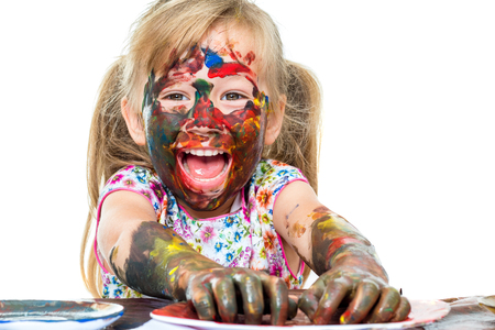 messing: Close up portrait of Excited little kid painting and messing with color paint.Isolated on white background.
