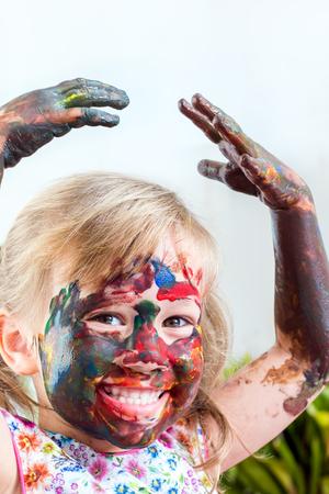 manos sucias: Close up retrato de niña cubierta con pintura de color que levanta las manos sobre la cabeza. Foto de archivo