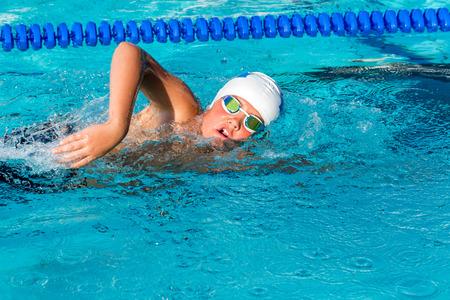 niños nadando: Cierre de tiro de la acción adolescente practicar estilo libre en la piscina. Foto de archivo