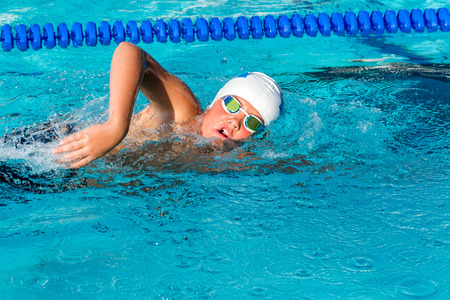 swimming goggles: Close up action shot of teenager practicing freestyle in swimming pool. Stock Photo