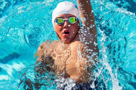 Close up action portrait of teen boy swimming backstroke.Top view of young swimmer with cap and goggles.