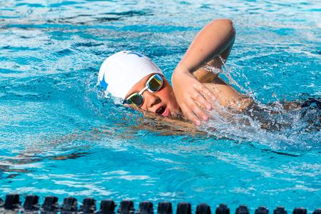 수영 수업에서 자유형을 하 고 십 대 학생의 액션 샷을 닫습니다.