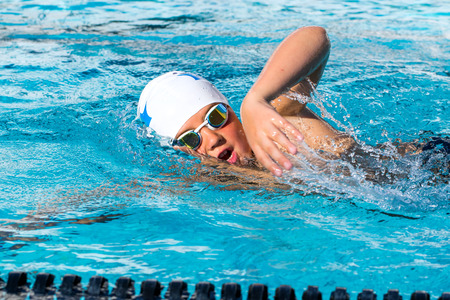 Close up action shot of teen student doing freestyle at swimming lesson. Stockfoto