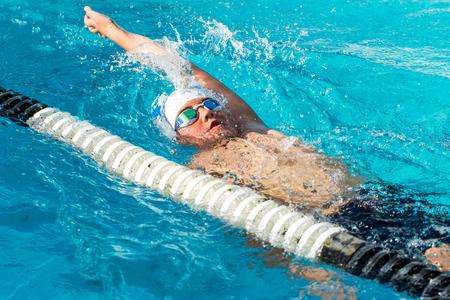nadar: Cierre de la acción de tiro de la natación Muchacho adolescente espalda en piscina.
