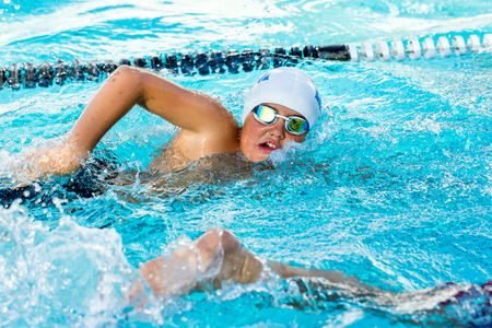 Close up action shot of teen boy competing at swimming gala.Young man doing freestyle.