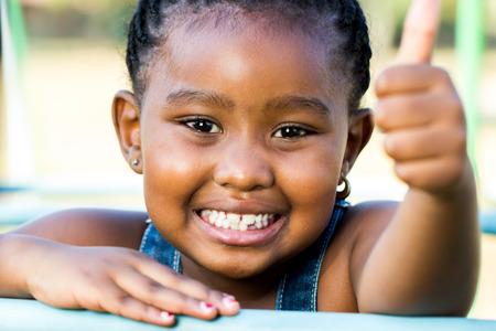 face shot: Close up face shot of little african girl doing thumbs up outdoors.