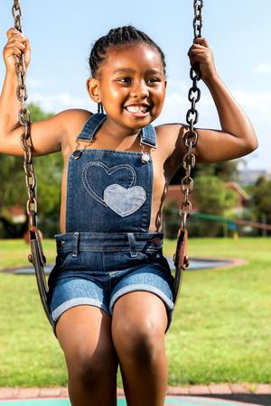niños jugando en el parque: Cerrar un retrato de la niña sonriente oscilante africano en el parque.