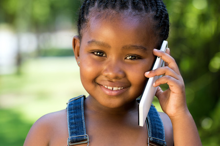 Close-up gezicht schot van schattige kleine Afrikaanse meisje praten op slimme telefoon tegen groene openlucht achtergrond.