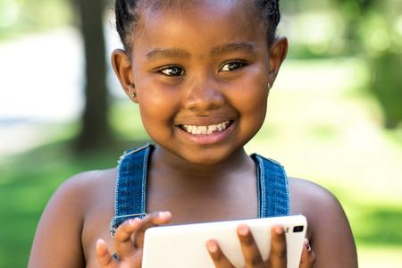 niños negros: Cerca retrato al aire libre de la niña africana linda que juega en la tablilla digital.