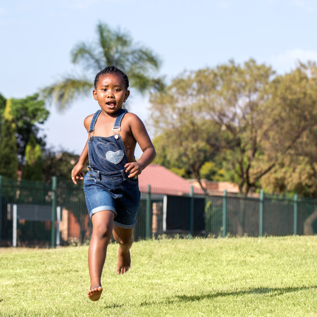 africa child: Close up action portrait of little african kid running in park.