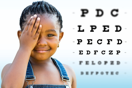 Close up Face shot of little African girl testing vision. Girl with braided hairstyle closing on eye with hand. Vision chart with block letters and focus point in background. Stockfoto