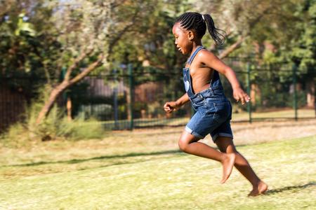 niñas jugando: Close up retrato acción del niño africano corriendo en el parque. Vista lateral de la niña con cola de caballo en movimiento.