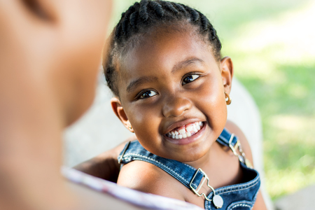 child laughing: Close up Face shot of little african girl laughing. Child looking at out of focus mother. Stock Photo