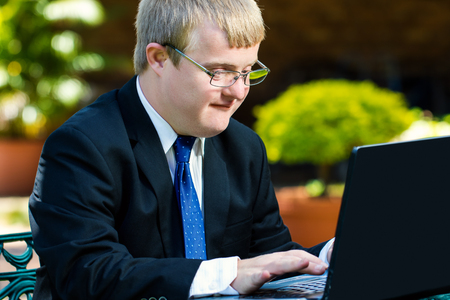 Close up portrait of businessman with down syndrome working. Young man in suit working on laptop in garden.