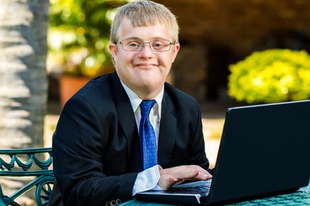 Close up portrait de jeune homme d'affaires avec le syndrome de Down faire la comptabilité sur ordinateur portable à l'extérieur.
