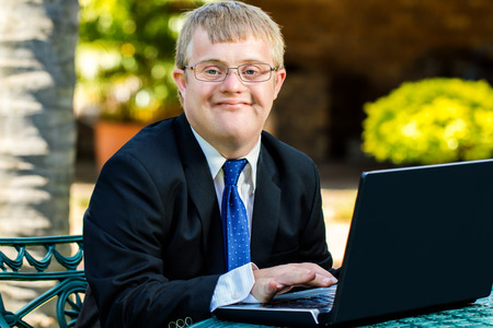 disadvantaged: Close up portrait of young businessman with down syndrome doing accounting on laptop outdoors.