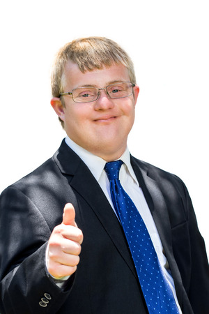 Close up portrait of young man with down syndrome in suit doing thumbs up symbol. Isolated against white background. Stock Photo