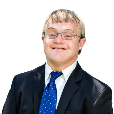 Close up face shot of friendly businessman with down syndrome wearing suit. Isolated against white background.
