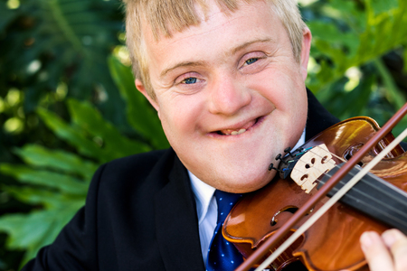 Close up portrait of handicapped violinist playing violin against green background. Stock Photo