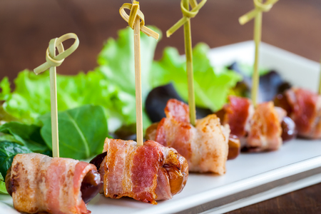 Macro close up of multiple date and bacon appetizers mounted on small skewers.