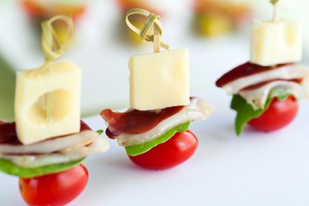 tomate cherry: Macro cerca de jamón de pato, queso y cereza de mini aperitivos tomate montados en los pinchos.