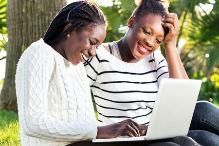 socializando: Cerca retrato al aire libre de dos muchachas adolescentes afro americano de socialización en la computadora portátil en el parque.