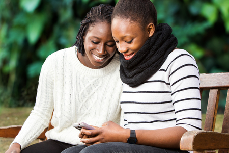 Close up portrait of two african american teenage girlfriends socializing on smart phone. Girls sitting on wooden bench in park against green background. Banque d'images