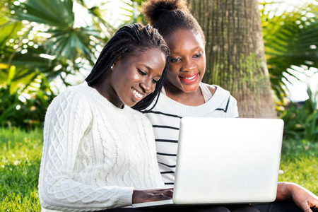 Close up outdoor portrait of two African teen girls typing on laptop in park. Stockfoto