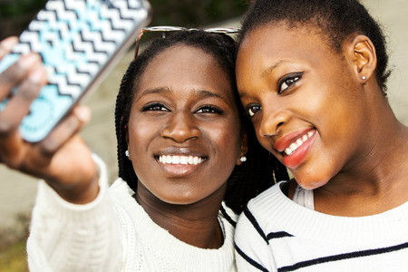 african american ethnicity: Close up face shot of two afro american teen girls taking self portrait with smart phone. Stock Photo