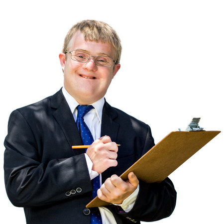 Close up portrait of young businessman with down syndrome writing on note board. Isolated against white background.