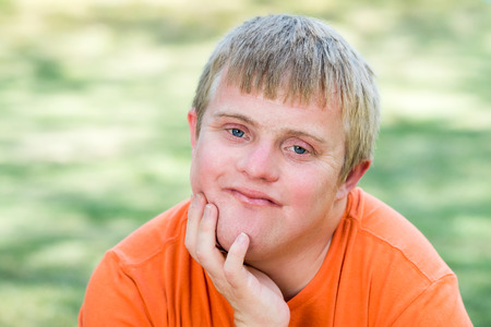 disadvantaged: Close up outdoor portrait of Handsome blue-eyed boy with down syndrome. Stock Photo