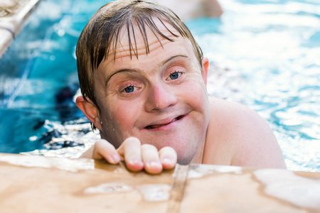 swimming: Close up face shot of handicapped boy in swimming pool. Stock Photo