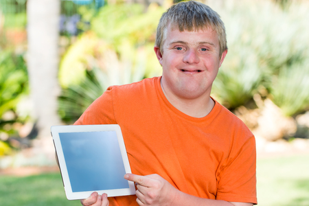 disadvantaged: Close up outdoor portrait of Young handicapped man pointing at blank tablet screen.
