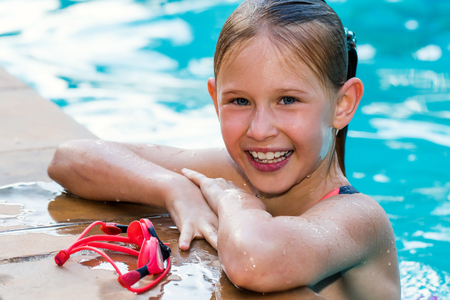 kids activities: Close up portrait of cute teen girl in swimming pool.