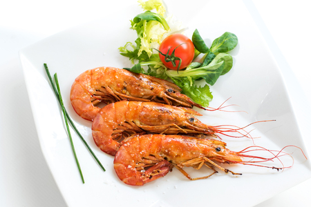 morsel: Macro close up top view of fresh grilled king prawns with green salad. Stock Photo