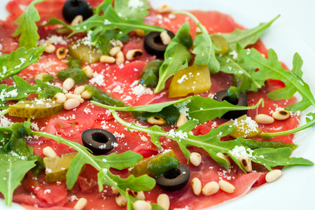 prepared dish: Macro close up of Beef carpaccio with rocket and olive dressing.