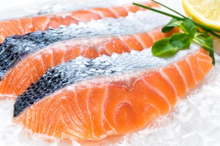 salmon ahumado: Macro cerca de porciones de salmón en rodajas frescas en hielo picado con limón y verdes en el fondo.