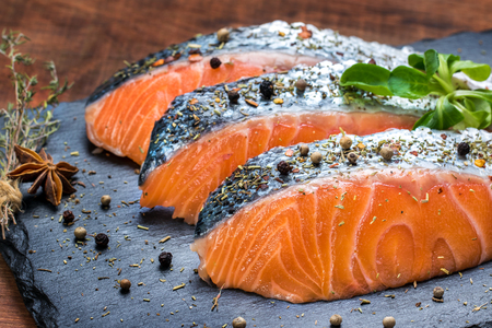 gastronomy: Macro close up of smoked salmon portions seasoned with aromatic herbs.