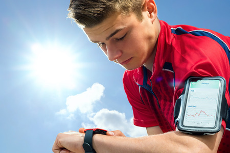 bluetooth: Close up portrait of young sports man reviewing activity tracker on smart watch. Teen boy wearing armband with smart phone against back light sun.