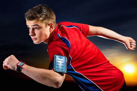 Close up portrait of handsome teen sports man with activity app on digital devices. Young man wearing armband with smart phone and smart watch against sunset background. photo