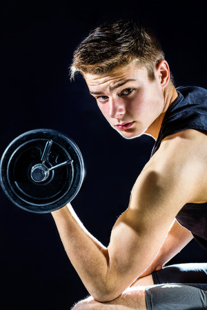 Handsome teen boy with working out with dumbbell. Isolated against black background. photo