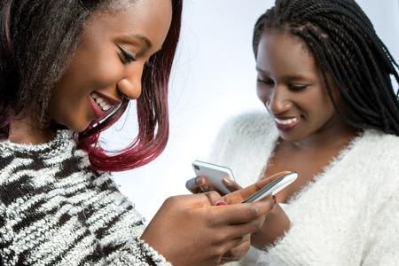 스마트 휴대 전화에서 연주 두 아프리카 십 대 소녀의 초상화를 닫습니다.